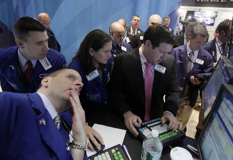 Specialists Jennifer Klesaris and William Bott, right center, work at a post on the floor of the New York Stock Exchange on Tuesday. Concern over the potential collapse of a bailout for Greece roiled the markets.