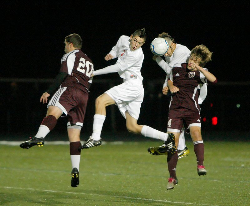Mitch Hodge, left, and Robbie Lentine of Windham compete for the ball with J.D. Hermann and Andrew Jones of Scarborough.