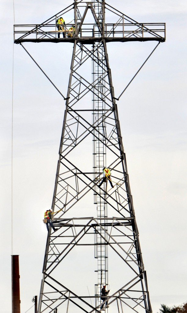 Central Maine Power employees work on a massive power line structure on a Kennebec River island in Farmingdale on Thursday. Maine weathered the late October snowstorm relatively well, but great swaths of southern New England remained without power for a fifth day, the AP reported Thursday.