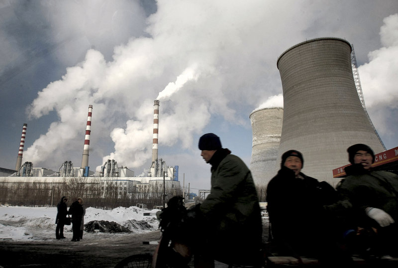 Workers pass a coal-fired power plant on a tricycle cart in Changchun, in northeast China's Jilin province last year. The world's emissions of heat-trapping carbon dioxide took the biggest jump on record in 2010, the U.S. Department of Energy calculated.