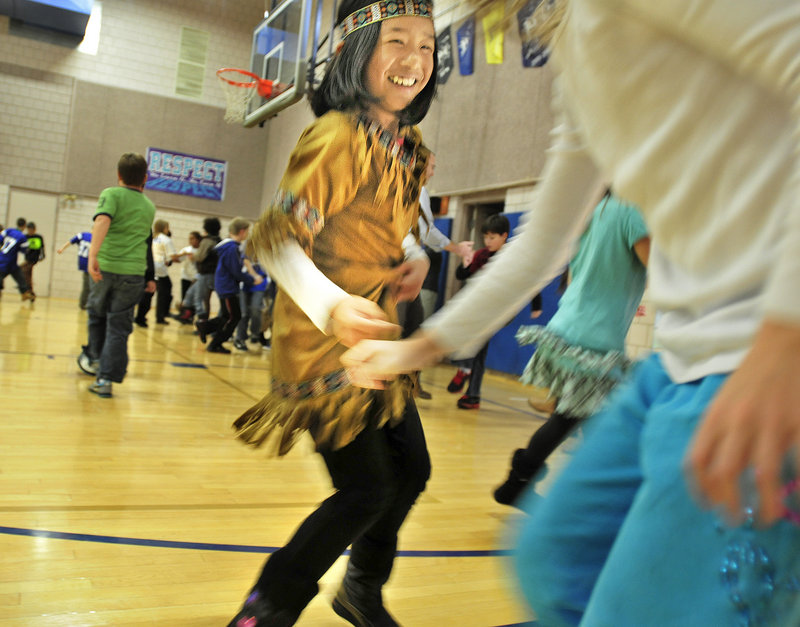 Abby Cotton, left, a Sea Road School fifth-grader, performs the mosquito dance with classmate Grace Thompson, right, to show their parents what they'd learned from the school's artist in residence.