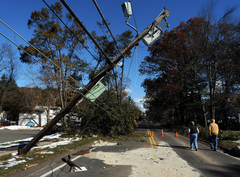 """Joyce and Bob Mercik walk around a snapped utility pole on a closed road Friday in Enfield, Conn. Repair crews with Connecticut Light & Power have felt the wrath of customers as the utility struggles with what it calls """"historic"""" outages."""