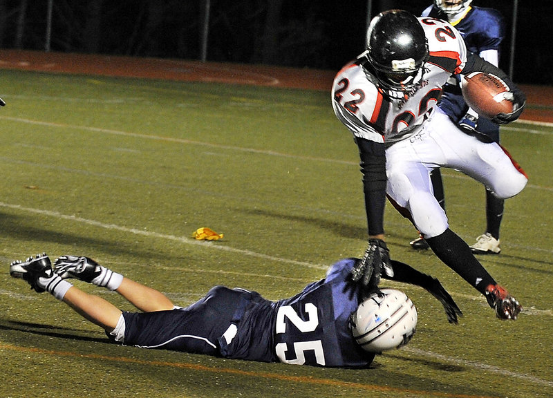 Quincy Thompson of Lisbon keeps his balance while attempting to dodge past Matt Woodbury of Yarmouth during the first half of Yarmouth's 38-0 victory Friday night.