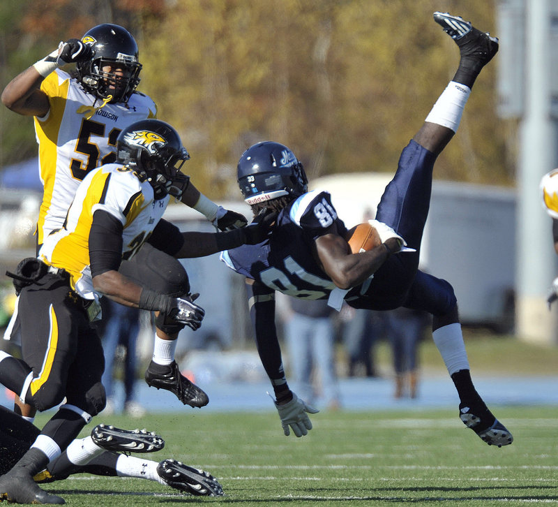 Denzel White, 52, and Tye Smith of Towson tackle UMaine's Maurice McDonald after a reception in Saturday's game at Orono. The Black Bears were beaten, 40-30.