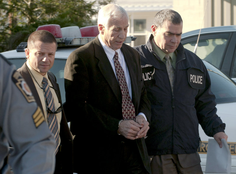 Jerry Sandusky, center, former defensive coordinator for the Penn State football team, is escorted to a police car Saturday in Bellefonte, Pa. He is charged with sexually abusing eight boys.
