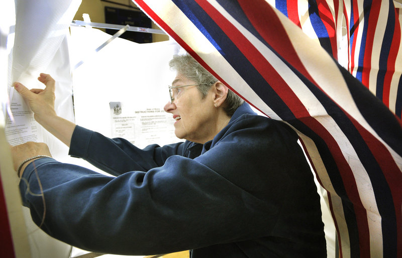 Voting registrar Betsy Jo Whitcomb tapes instructions and other notices inside voting booths Monday at Falmouth High School. Falmouth and the rest of Cumberland County will vote today on a $33 million bond issue for civic center repairs.