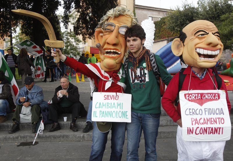 "Among the thousands of Democratic party demonstrators seeking the ouster of Premier Silvio Berlusconi were these two in Rome on Saturday. They are wearing masks and signs mocking Berlusconi, right, and Reform Minister Umberto Bossi. The placards say ""Silvio, change my diaper,"" left, and ""I'm looking for confidence, payment in cash."""