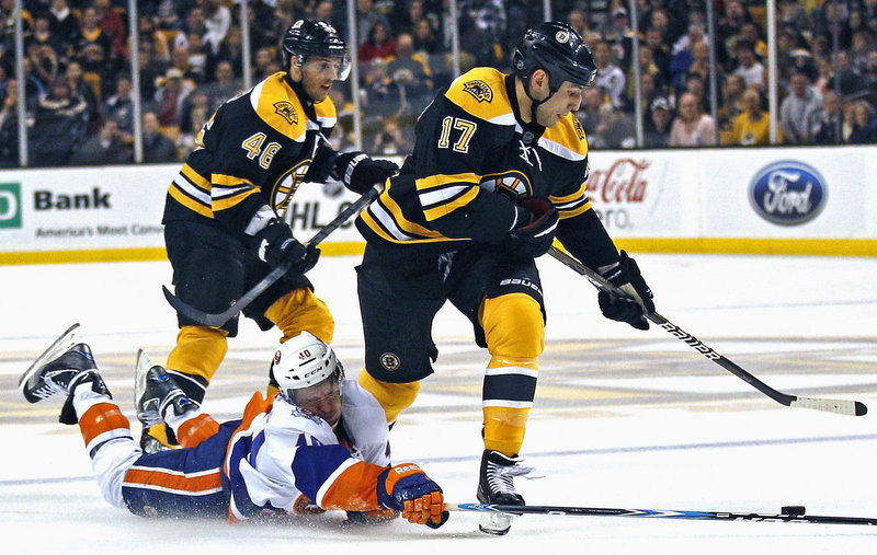 Michael Grabner of the Islanders tries to knock the puck free from Boston's Milan Lucic in Monday night's game in Boston. The Bruins won their third straight, 6-2.
