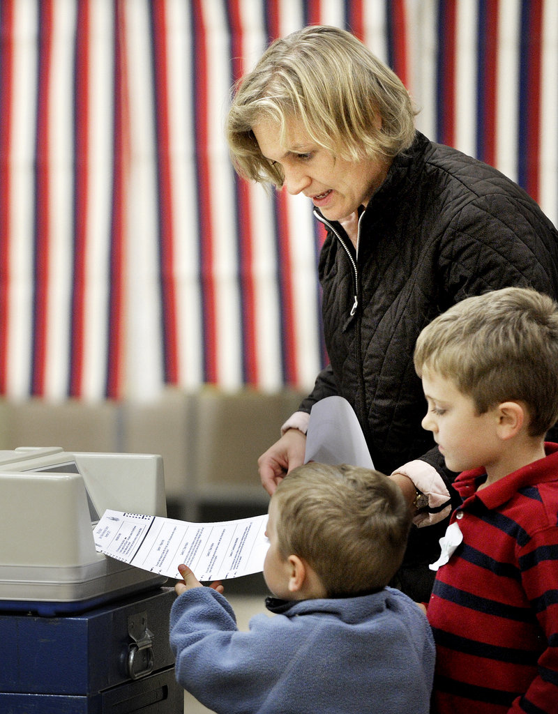 Reid, 3, and Henry, 5, help their mom, Amy Haile, cast her ballot in Westbrook on Tuesday night.