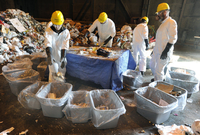 A crew hired by the University of Maine sorts trash Wednesday at the ecomaine waste plant in Portland for a study on recycling. The crew sorted about 400 pounds of trash collected in Scarborough into 30 bins.