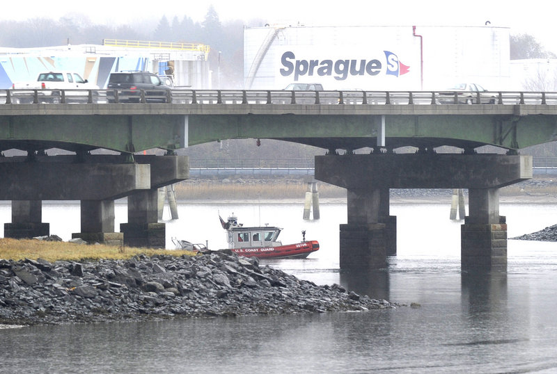 A Coast Guard vessel stands by under an I-295 overpass as a cleanup crew works along the Fore River at the end of a runway at the Portland International Jetport on Thursday.