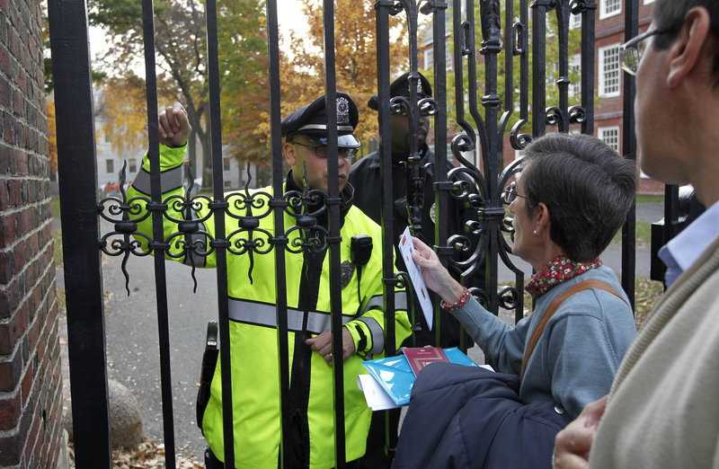 Olga Fradejas, a Spanish teacher at Harvard University, second from right, is turned away from an entrance to the school by police in Cambridge, Mass., Thursday. Police told her to use one of the school's designated open entrances. Olga Fradejas, a Spanish teacher at Harvard University, second from right, is turned away from an entrance to the school by police in Cambridge, Mass., Thursday. Police told her to use one of the school's designated open entrances.