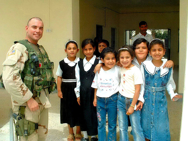 Army Capt. Christopher Cash, a soldier with roots in Maine, poses with Iraqi schoolchildren on the day before he was killed in a firefight with insurgents in Baqubah, Iraq, in 2006.