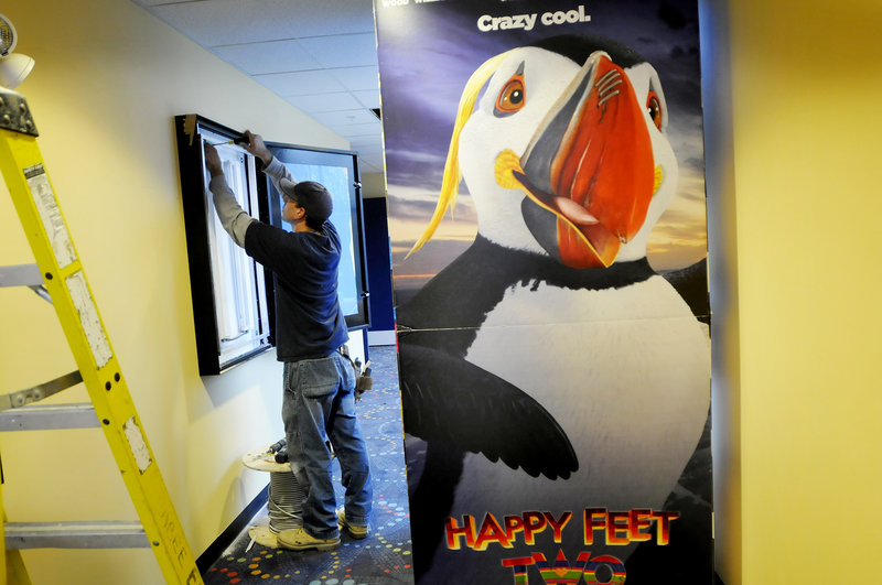 Kevin Ruel of Seabee Electric works on what will be a poster board display at the new Nordica Theatre. To the right is a display for the movie Happy Feet Two, which will show in 3-D during the theater s first week in business.