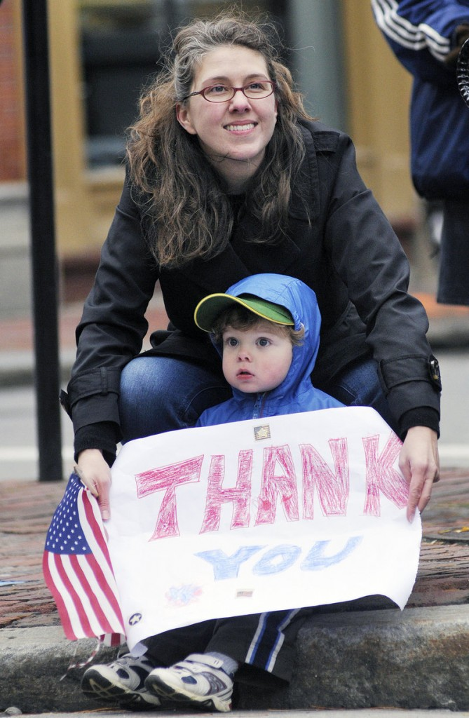 Emily Read of Scarborough and her son Teddy, 2, show their support for veterans during the Veterans Day Parade in Portland on Friday. Dozens of marchers representing veterans, military units and the city's police and fire departments marched from Longfellow Square to City Hall.