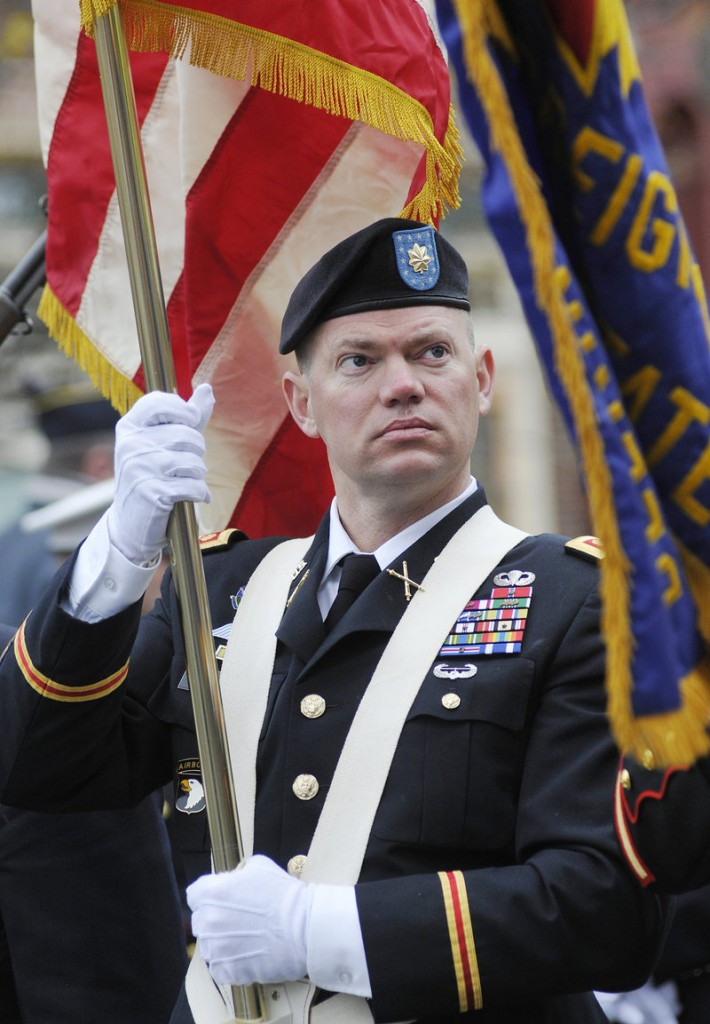 Maj. Todd Mitchell, a color guard with Veterans of Foreign Wars Post 6859, carries the colors before the start of the Veterans Day parade in Portland on Friday. Mitchell served in the Army.