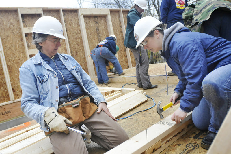 Karen Boudriault of Waterboro and Karen Hewes of South Portland work to help Habitat for Humanity build houses in Freeport on Friday. Habitat for Humanity is building three homes for low-income families on South Street.
