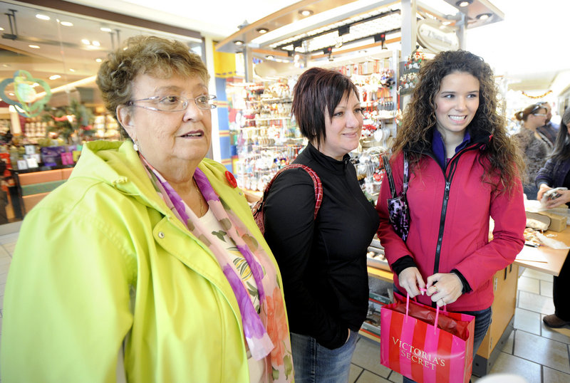Three generations – grandmother Helen Mac Mullin, left, daughter Suzanne Porter, middle, and granddaughter Jessica Bushell from Cape Breton, Nova Scotia – get a lot of their Christmas shopping done at the Maine Mall on Saturday.