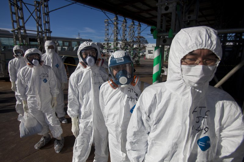 Workers in protective suits and masks wait to enter the emergency operation center at the crippled Fukushima Dai-ichi nuclear power station on Saturday. Reporters who were allowed to tour the plant found that much progress has been made but that years of work lie ahead.