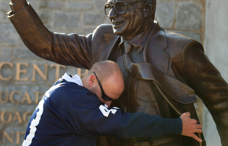 Penn State fan Gary Buck of West Grove, Pa., hugs a statue of former Penn State head coach Joe Paterno at Beaver Stadium before Saturday's football game between the University of Nebraska and Penn State in State College, Pa.
