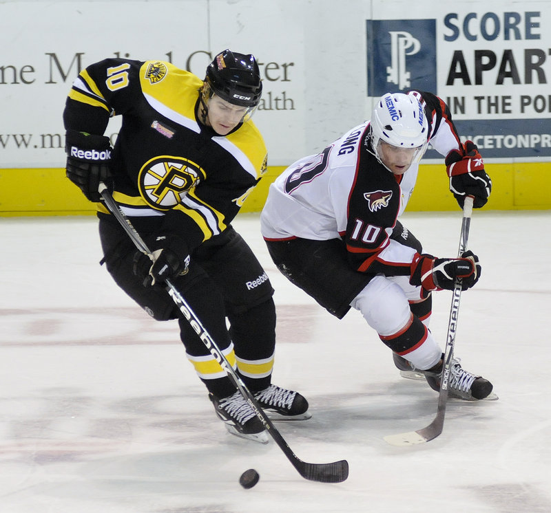 Shawn Patrick Ouellette/Staff Photographer Colin Long of the Portland Pirates goes for the puck against Providence's Kyle Mac Kinnon in Saturday night's game at the Cumberland County Civic Center. The Pirates ended a two-game losing streak with a 4-2 win.