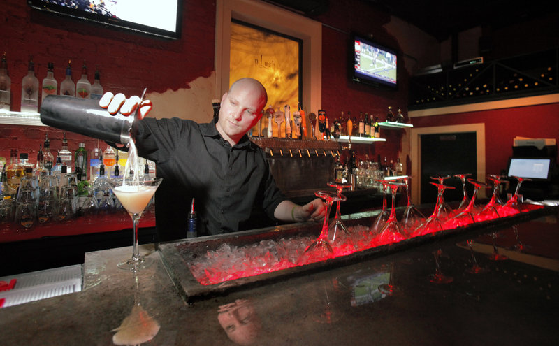 Bar manager Sean Steinmark, above, pours a Rangtang Cosmo at Plush West End in Portland, which comfortably fills the space occupied for years by Katahdin restaurant.