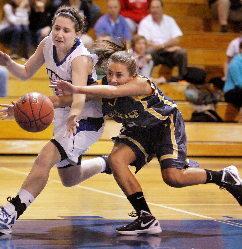 Haley Jordan of the University of Southern Maine, right, reaches to knock the ball from Kelly Coleman of the University of New England during UNE's 65-63 victory in a women's basketball opener Tuesday night.