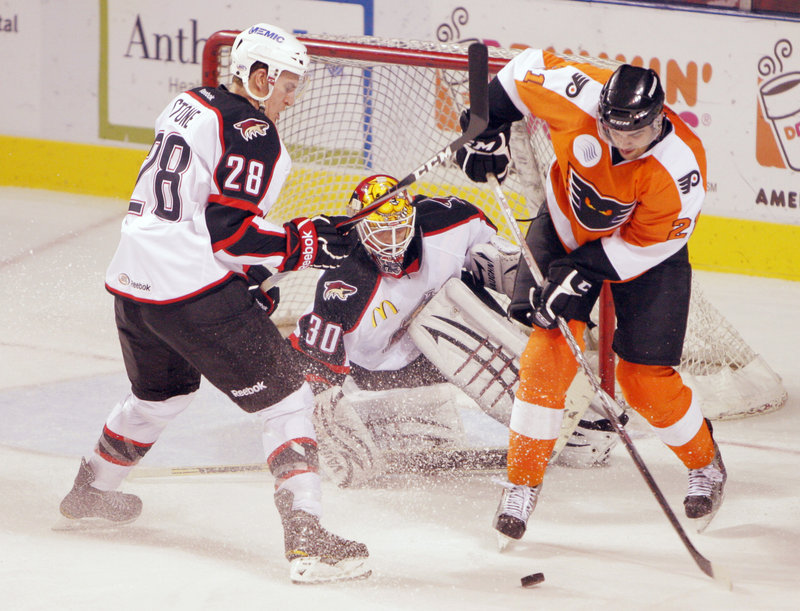 Tom Sestito of the Philadelphia Phantoms, right, attempts to turn for a move on Pirates goalie Marc Cheverie as defenseman Michael Stone helps out Tuesday night during Portland's 4-2 victory at the Civic Center.