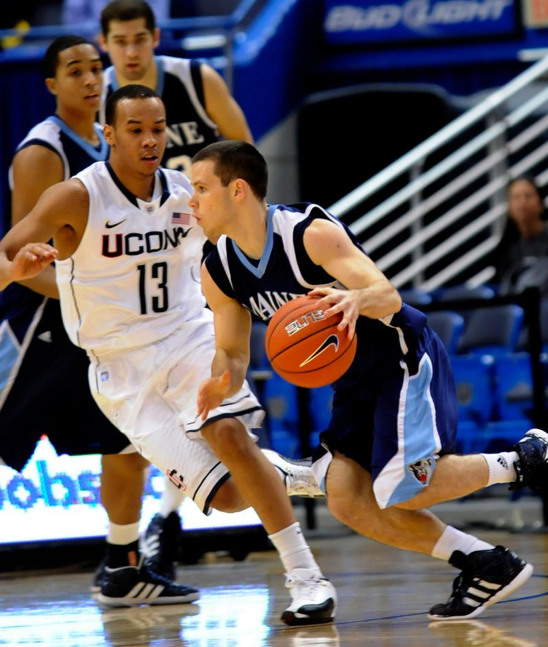 Maine guard Andrew Rogers drives against Connecticut's Shabazz Napier during Thursday's game in Hartford, Conn. Maine lost to the reigning NCAA champs, 80-60.
