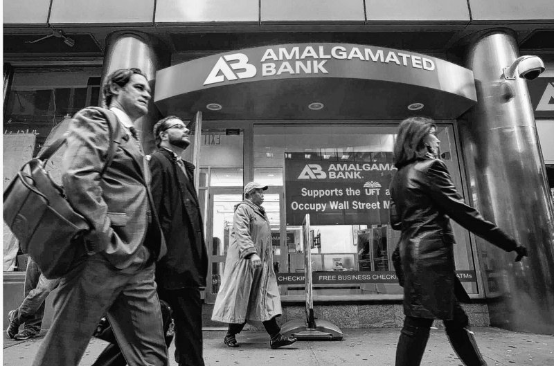 Pedestrians pass the Amalgamated Bank at 52 Broadway in lower Manhattan in New York earlier this month. Amalgamated Bank, a union-owned bank founded in 1923, supports the Occupy Wall Street movement.
