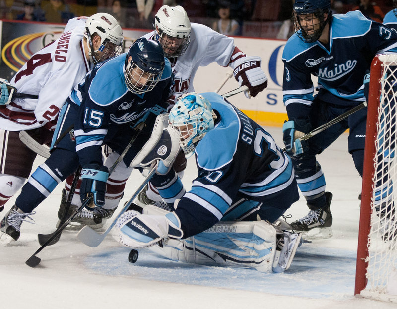 Maine goalie Dan Sullivan stays with the puck Friday night with help from defenders John Parker, left, and Mark Nemec as Massachusetts unleashes its offense during a 2-2 tie in a Hockey East game at Amherst, Mass.