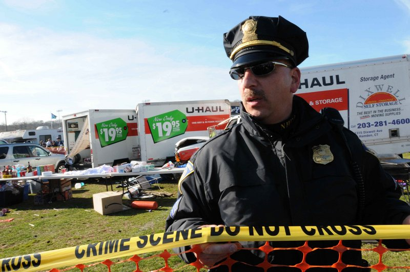Police investigate the scene of an accident at a Yale Bowl parking lot before the football game between Yale and Harvard on Saturday in New Haven, Conn. The driver of a rental truck carrying beer kegs through a parking area before the game suddenly accelerated, fatally striking a 30-year-old woman and injuring two others, police said. The truck then crashed into other rental vans in the lot.