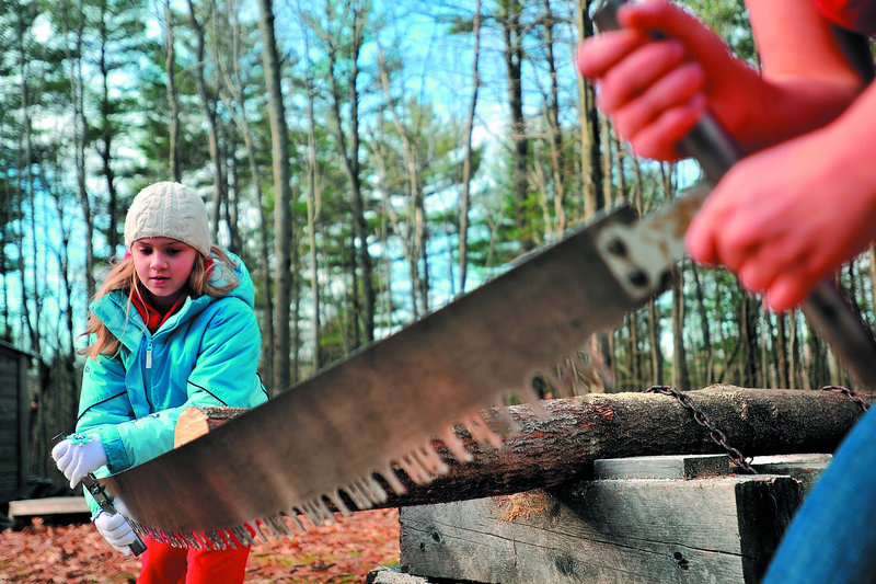 Emma Parrish, 9, of Oakland learns to use a crosscut saw with the help of Colby sophomore Liz Schell as part of the Adventure Girls program on Saturday at the college in Waterville.