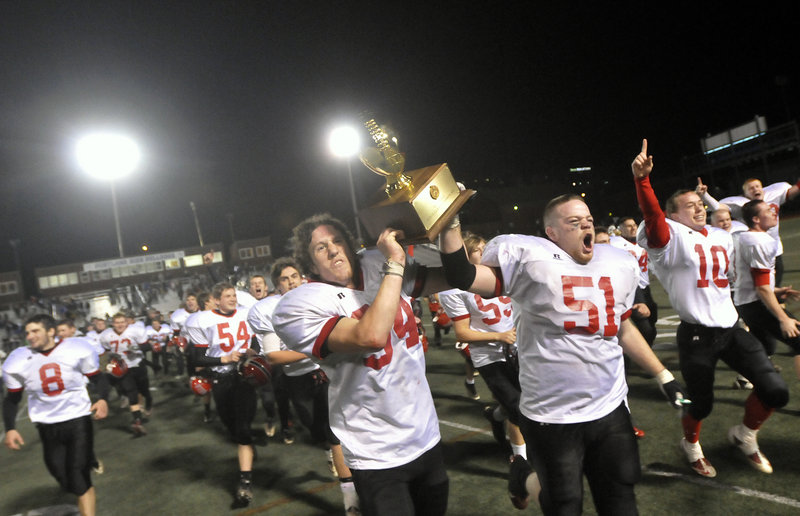 The Wells team, led by Louis DiTomasso and Andrew Staples, carries the trophy to the Wells fans after winning the Class B championship Saturday.
