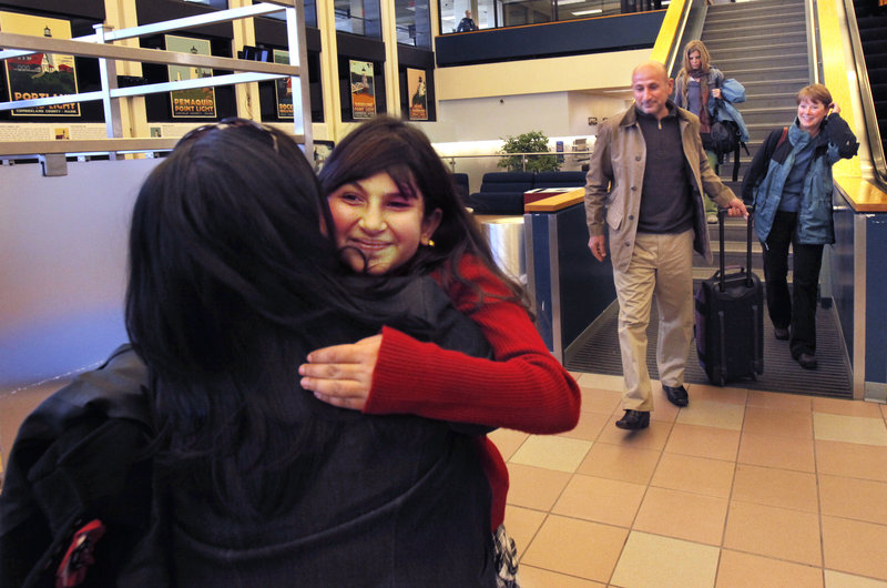 Noora Afif Abdulhameed hugs Tasha Horton after arriving at the Portland International Jetport with her father, Afif, on Monday.