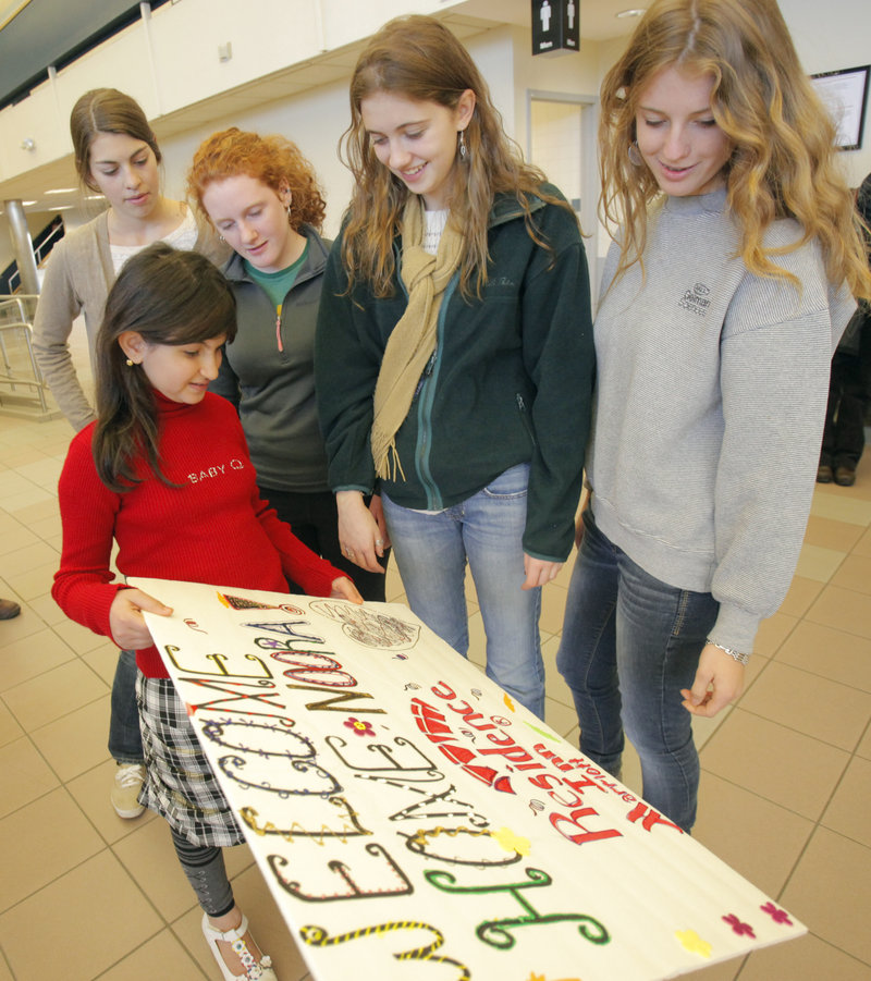 Noora Afif Abdulhameed shows a sign to Falmouth High students, from left, Marian Bergkamp, Clara Brown, Caroline Levy and Nevada Horne after her arrival Monday. The students will be doing art projects with Noora at the Ronald McDonald House.