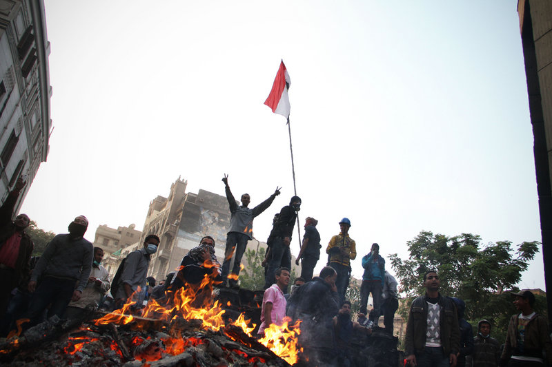 A protester flashes the victory sign Monday during clashes with riot police in Cairo. Security forces fired tear gas at several thousand protesters in the third day of violence that has killed at least 26 people and has turned into the most sustained challenge yet to the rule of Egypt's military.