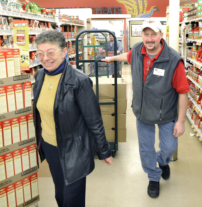 Debi Hubbard gets help Tuesday from meat manager Wally Bennett as she picks up 24 turkeys at Hannaford in South Portland for the Thanksgiving dinner she cooks at the VFW hall.