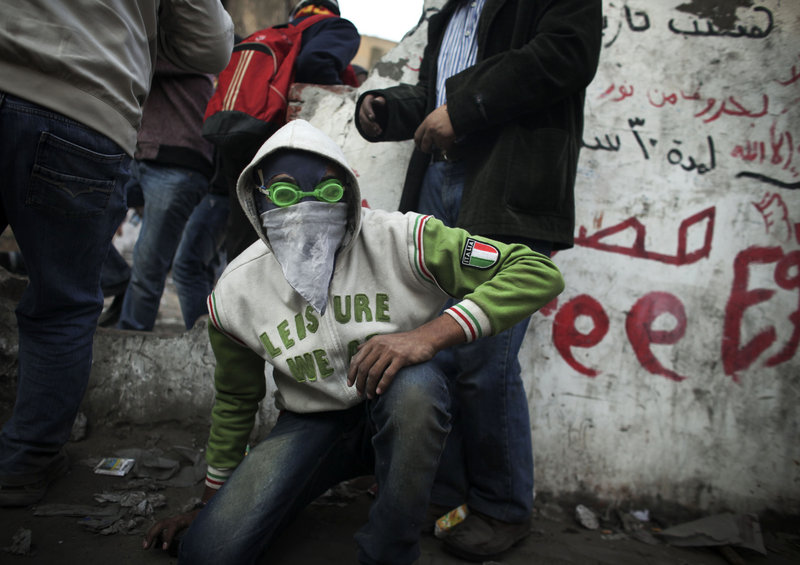 A protester wearing swimming goggles crouches as riot police fire tear gas Tuesday near Tahrir Square. The military said it would move up presidential elections to early 2012.