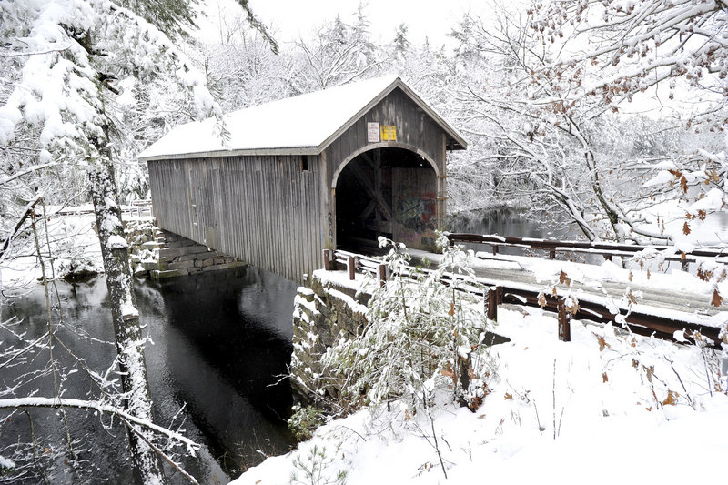 A covered bridge over the Presumpscot River in Windham sports a coat of white after a storm dumped up to 15 inches in some areas.
