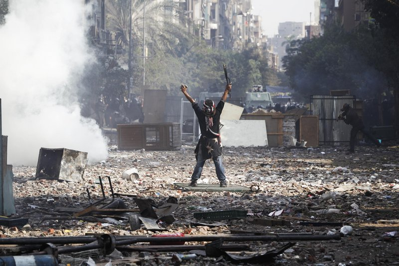 A protester gestures to Egyptian riot police during clashes near Tahrir Square in Cairo on Wednesday. The United Nations condemned the violence.