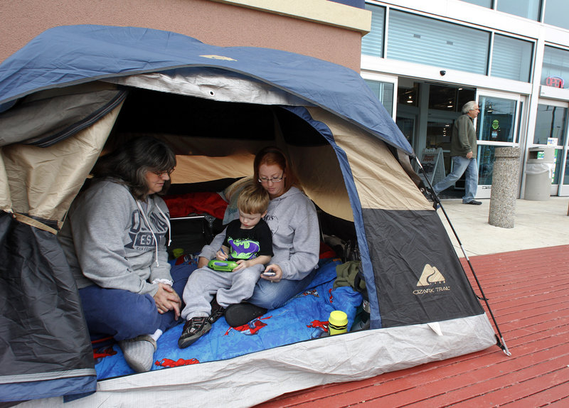 Nicki Lawrence, left, her daughter Windy LaFerney and grandson Caisen, 4, wait in their tent in front of Best Buy in Mesquite, Texas, on Monday. They set up their tent late Sunday so they can be first in the store Friday to get a deal on a TV and other items for Christmas.