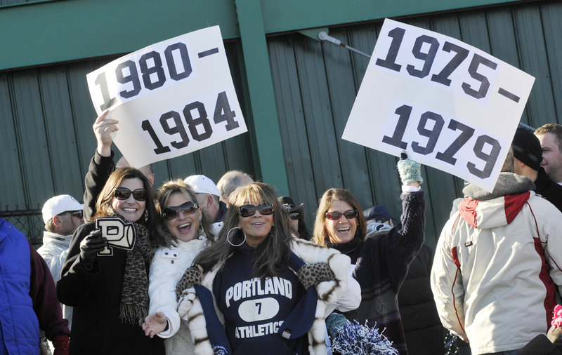 Former Portland High students, from left, Kelly Hasson, Theresa DiPietro, Lucia DiPietro Benatar and Lisa Martin show off their pride as alumni get together for a halftime ceremony during the annual Thanksgiving Day football game between crosstown rivals Deering and Portland at Fitzpatrick Stadium in Portland on Thursday.