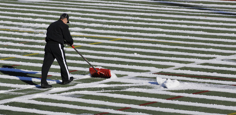 Kevin Martin shovels snow from the field before the start of Thursday's game. Deering beat Portland, but many football fans say the score isn't what matters.