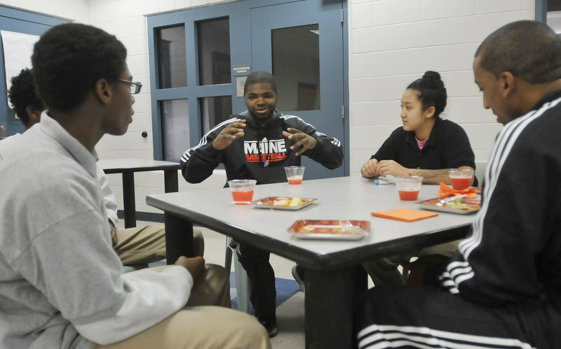 """Darren Cooper of the Red Claws shares a story with youth center residents. Listening, from left, are Keelin White, Deeka Loth and Red Claws player JR Reynolds. Long Creek basketball coach Chad Sturgis said the interaction is exciting for his players. """"It motivates them,"""" he said."""