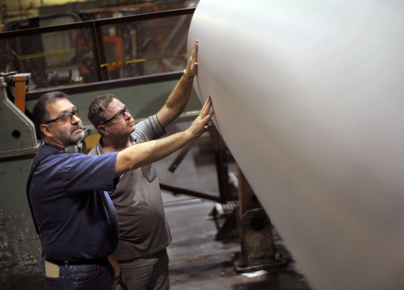 Rick Nicholson, left, and Louis Ouellette inspect a roll of paper on the operation floor of the Great Northern Paper Co. mill in East Millinocket this week. Idled for months, the mill is back in operation, making newsprint and employing more than 200 paper-makers. The prospect of continued investment has provided a glimmer of hope for workers in a region that's rich in natural resources but short on jobs.