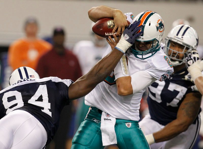 Miami quarterback Matt Moore attempts to hold the ball Thursday while being sacked by DeMarcus Ware of the Dallas Cowboys during the Cowboys' 20-19 victory.