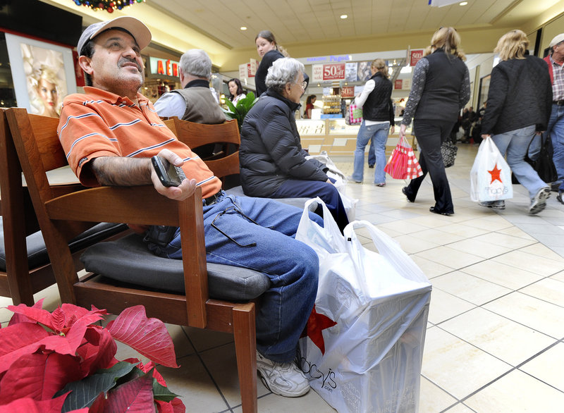 Kiam Hajizadeh of Falmouth, whose family started shopping at 6 a.m. Friday, waits for his wife and their two children at the Maine Mall.