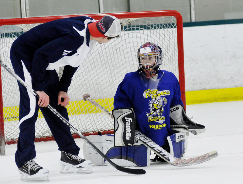 Jacob Veilleux, 9, of Yarmouth receives some goaltending tips from one of the Black Bears' goalies, Martin Ouellette.