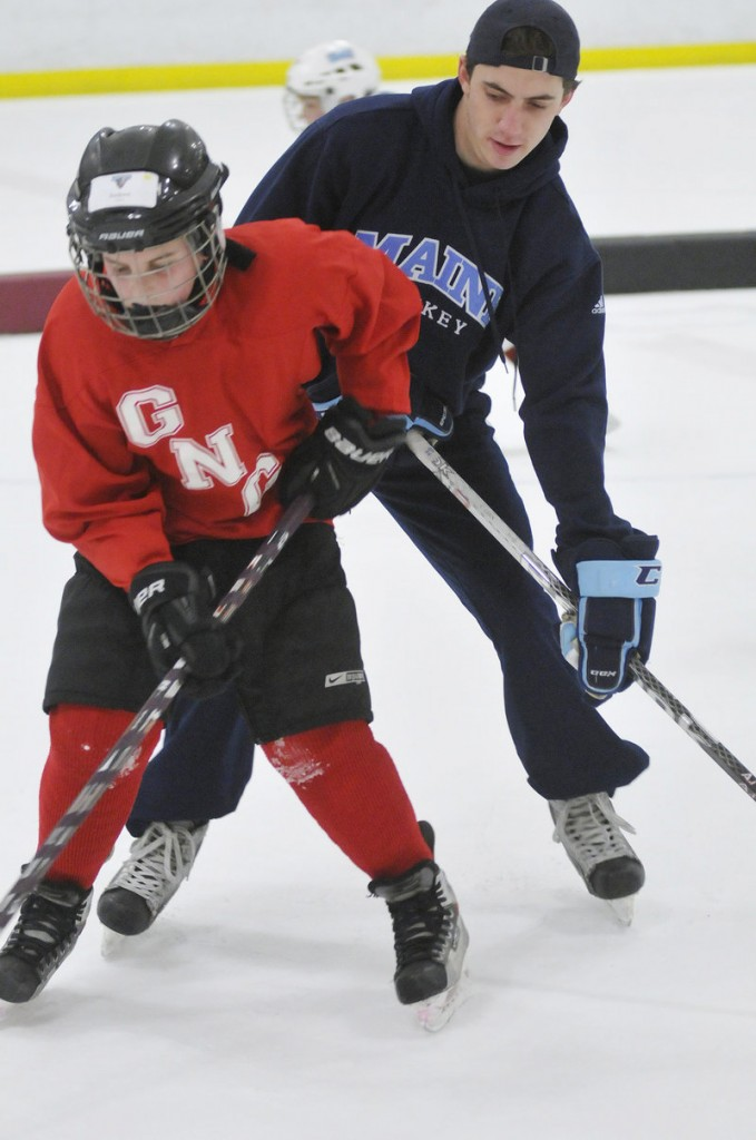 Andrew Topham, 10, of Gray tries to keep the puck from Connor Leen of UMaine during a drill as part of the clinic for Casco Bay Youth Hockey players.